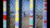 Two people embrace on the U.S. side of the border, seen through the border wall Monday, Jan. 7, 2019, seen from along the beach in Tijuana, Mexico. (AP Photo/Gregory Bull)