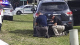 Law enforcement officials take cover outside a SunTrust Bank branch, Wednesday, Jan. 23, 2019, in Sebring, Fla. Authorities say they've arrested a man who fired shots inside the Florida bank. (The News Sun via (AP)