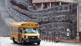 In this Monday, Feb. 4, 2019, photo, a school bus rolls past the concertina wire-covered fence at East International and Nelson Streets in downtown Nogales, Ariz. Photo: Jonathan Clark/AP