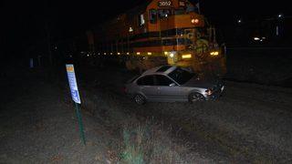 Oregon man unhurt when stuck car hit by train