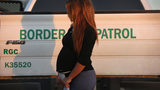 An immigrant from El Salvador, seven months pregnant, she said, stands next to a U.S. Border Patrol truck after turning herself in to border agents on December 7, 2015 near Rio Grande City, Texas. Photo: John Moore/Getty Images