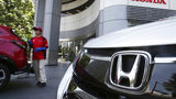 FILE - In this July 31, 2018 file photo, an employee of Honda Motor Co. cleans a Honda car displayed at its headquarters in Tokyo.
