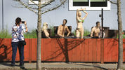 In this photo taken Monday, March 18, 2019, a woman stops to photograph a display of mannequins in Santa Rosa, Calif. Homeowner Jason Winduce set up the display, after a neighbor in the area complained to the city about his six-foot-tall fence.