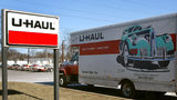 A U-Haul truck sits in front of a U-Haul store.