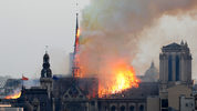 Flames rise from Notre Dame cathedral as it burns in Paris, April 15, 2019. Massive plumes of yellow brown smoke is filling the air above Notre Dame Cathedral and ash is falling on tourists and others around the island that marks the center of Paris.