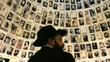FILE PHOTO: An ultra-Orthodox Jew looks at photographs of Jewish victims of the Nazis in the Hall of Names exhibit in the Yad Vashem Holocaust Memorial museum May 4, 2005 in Jerusalem, Israel.