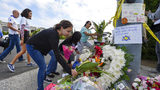 A group of Poway residents bring flowers and cards to a memorial outside of the Chabad of Poway synagogue, Sunday, April 28, 2019, in Poway, Calif. A man opened fire Saturday inside the synagogue near San Diego on the last day of Passover.