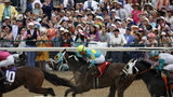 People cheer as they watch a race at Churchill Downs before the 145th running of the Kentucky Derby horse race Saturday, May 4, 2019, in Louisville, Ky. (AP Photo/John Minchillo)