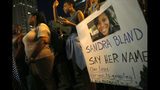 A demonstrator holds a Sandra Bland sign during a candlelight vigil July 28, 2015, near the DuSable Bridge on Michigan Avenue in Chicago. Photo: AP Photo/Christian K. Lee