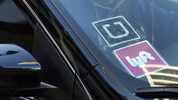 A ride-share car displays Uber and Lyft stickers on its front windshield in a 2016 photo taken in downtown Los Angeles. A federal civil jury on Tuesday, May 21, 2019, found a former Somali army colonel, Yusuf Abdi Ali, liable for the torture of a