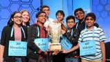 The eight co-champions of the National Spelling Bee pose with the winner's trophy.