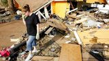 FILE - In this Sept. 24, 2008, file photo, Gina Hadley walks through what's left of her home in the aftermath of Hurricane Ike in Galveston, Texas.