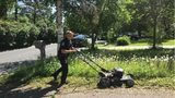 Orono police Officer Matt Siltala is hard at work as he cuts a woman's lawn Thursday.