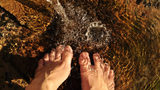 Stock photo of feet in the water.