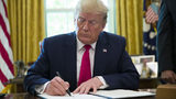 President Donald Trump signs an executive order to increase sanctions on Iran, in the Oval Office of the White House, Monday, June 24, 2019, in Washington.
