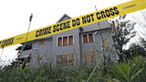 Crime scene tape cordons off a boarded-up home July 22, 2013, in an area where the bodies of three slain women were found in garbage bags in East Cleveland, Ohio. AP Photo/Mark Duncan
