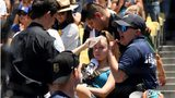 A young woman holds an ice pack to her head as she is taken by a stretcher from her seat at Dodger Stadium on Sunday. The fan was hit by a foul ball off the bat of Dodgers rightfielder Cody Bellinger.