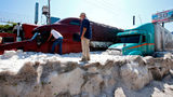 Men remain next to trucks buried in hail in the eastern area of Guadalajara, Jalisco state, Mexico, on June 30, 2019. - The accumulation of hail in the streets of Guadalajara buried vehicles and damaged homes.