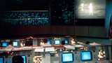 This July 20, 1969 photo shows the Mission Operations Control Room in the Mission Control Center during the Apollo 11 lunar landing. The television monitor shows astronauts Neil A. Armstrong and Edwin E. Aldrin Jr. on the surface of the moon.