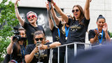 Members of the U.S. women's soccer team, including Megan Rapinoe, rear left, and Alex Morgan, right foreground, stand on a float before being honored with a ticker tape parade along the Canyon of Heroes in New York. (AP Photo/Craig Ruttle)