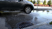 A car drives through water that is leaking from a manhole in California. The city of Berkeley, California, will use gender-neutral language in its municipal codes.