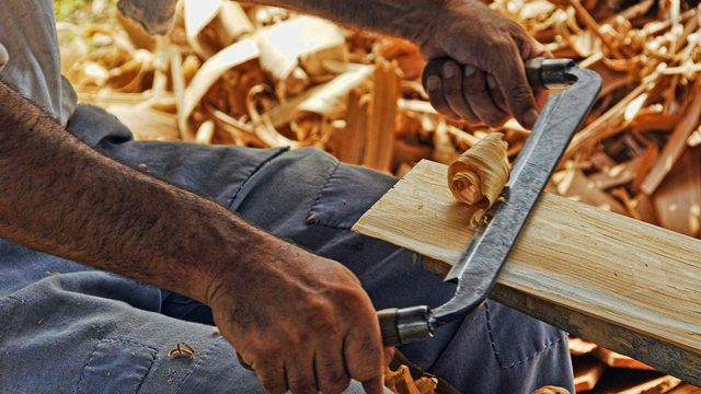 A man scraping a piece of wood