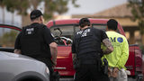 In this July 8, 2019 file photo, U.S. Immigration and Customs Enforcement (ICE) officers detain a man during an operation in Escondido, California.