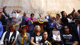 Supporters of a bill limiting the police use of deadly force surround Gov. Gavin Newsom, center, during a signing ceremony in Sacramento, Calif., Monday, Aug. 19, 2019.