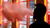 FILE - In this Feb. 20, 2014, file photo, a patron exhales vapor from an e-cigarette at a store in New York. New York Gov. Andrew Cuomo announced emergency executive action to ban the sale of flavored e-cigarettes.