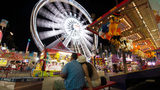 FILE PHOTO: Visitors attend the Los Angeles County Fair 2013 in Pomona, California. Police said a 22-year-old man emailed a hoax threatening violence at the fair to avoid going with his parents.