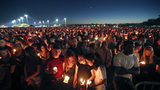 In this Feb. 15, 2018, file photo, people attend a candlelight vigil for the victims of the shooting at Marjory Stoneman Douglas High School in Parkland, Fla.
