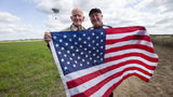 A  98-year-old American WWII veteran, Tom Rice, and U.S. Ambassador Pete Hoekstra, right, pose with the U.S. flag after Rice landed in a tandem parachute jump near Groesbeek, Netherlands, Thursday, Sept. 19, 2019, with the 101st Airborne Division.