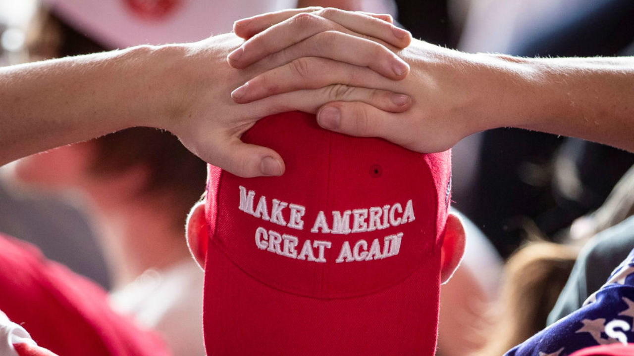Community rallies to support high school cheerleaders holding MAGA banner