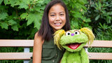 "This undated image released by Sesame Workshop shows 10-year-old Salia Woodbury, whose parents are in recovery, with ""Sesame Street"" character Karli. Sesame Workshop is addressing the issue of addiction."