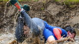 Molly and Patrick Kimball, of Augusta, Maine, tumble into some muddy water as they make their way through the course at  the North American Wife Carrying Competition.