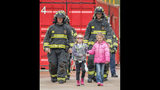 Olivia Gant, center, walks with firefighters in an April 2017 photo. Olivia's mother, Kelly Turner, is accused of murder, fraud and other charges in her Aug. 20, 2017, death. Authorities say Turner, 41, lied about her daughter being terminally ill.