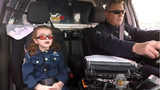Olivia Gant goes on a ride with a Denver police officer in a still from video shot in April 2017, about four months before the 7-year-old's death. Her mother, Kelly Turner, is accused of lying about the girl's health for years before killing her.