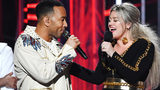 "FILE PHOTO: John Legend (L) and host Kelly Clarkson appear at the 2018 Billboard Music Awards. The duo remade the classic, but controversial, Christmas song ""Baby It's Cold Outside."""