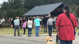 A crowd gathered with their heads bowed, surrounding a small urn with an American Flag at the Jacksonville National Cemetery.  (ActionNewsJax.com)