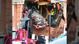 A Porsche is removed from the second story of a building after the convertible went airborne and crashed into the second floor of a New Jersey commercial building early Sunday, killing both of the car's occupants, in Toms River, N.J.