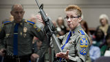 In this Jan. 28, 2013, file photo, firearms training unit Detective Barbara J. Mattson, of the Connecticut State Police, holds up a Bushmaster AR-15 rifle for a demonstration during a hearing at the Legislative Office Building in Hartford, Conn.