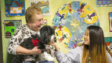 Cynthia Zeldin (left) allows Global Village project student Mu Doe (right) (last name withheld), 15, to pet Lily, a registered therapy dog, during their reading time at the Global Village Project school in Decatur.