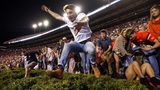 Jubilant Auburn fans vaulted the hedges and ran onto the field at Jordan-Hare Stadium after the Tigers beat rival Alabama in the Iron Bowl.